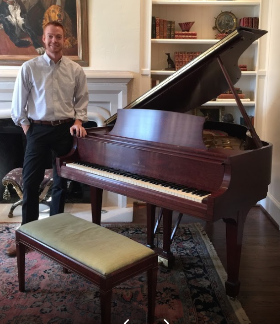 holt standing with a steinway piano